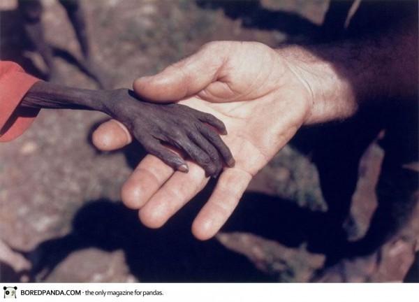 Avril 1980, Karamoj, Ouganda, Un missionnaire prend la main d'un enfant mourant de famine