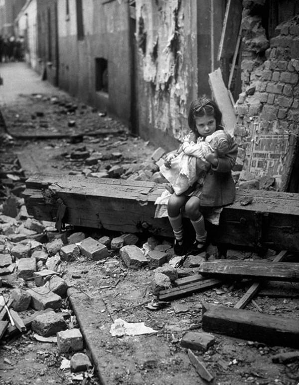 1940 : Un petite fille assise dans les ruines de sa maison à Londres