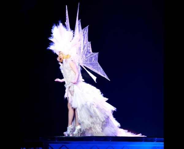 Gaga in a white leather bikini, angel wings, and a giant glittering headpiece