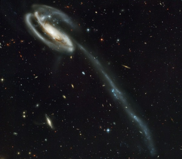 A wallpaper of distant galaxies is a stunning backdrop for a runaway galaxy